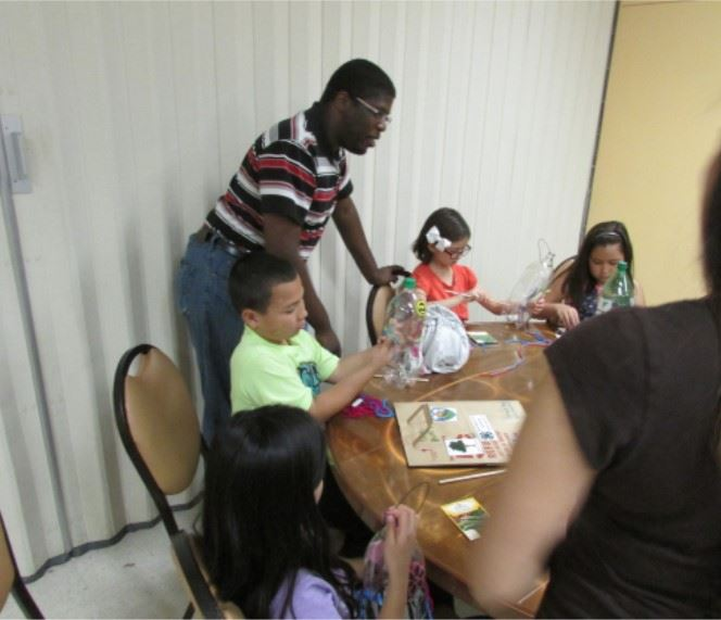 A volunteer assists children with a craft project
