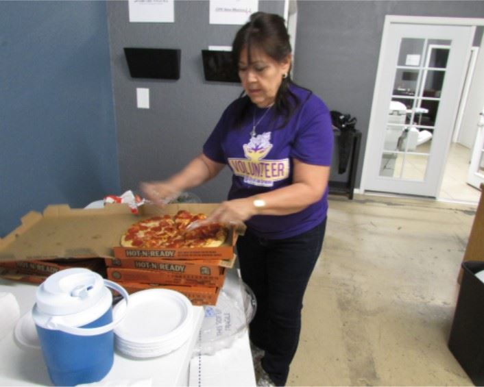 A volunteer sets out pizza for people to eat