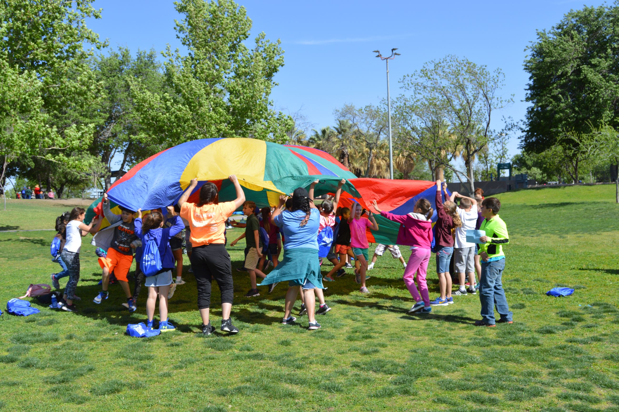 Kids playing wtih a giant parachute