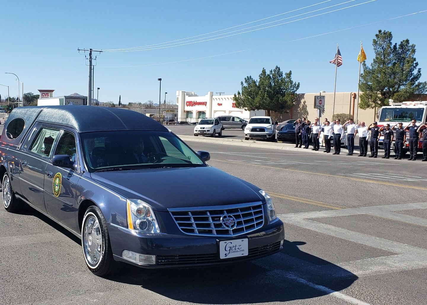 City of Las Cruces firefighters and police officers pay their respects as the hearse carrying Sgt. 1