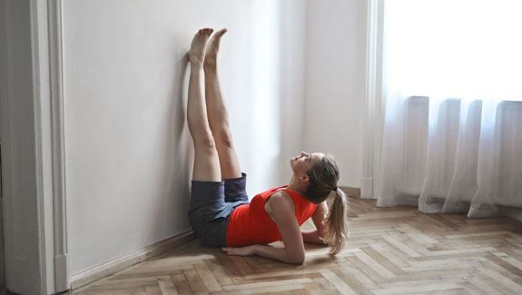 Woman with legs stretching up against wall